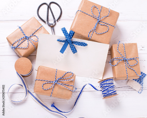 Empty tag and wrapped gift boxes with presents, scissors and blue ribbon
