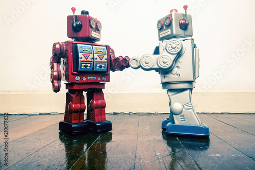 Obraz two vintage robot shake hands on a old wooden floor - fototapety do salonu