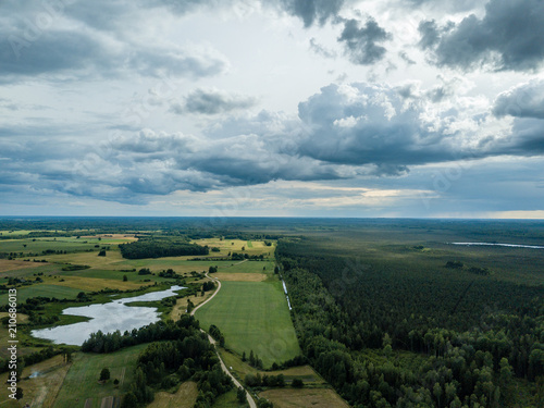 Deurstickers Bleke violet drone image. aerial view of rural area with houses and roads under heavy rain clouds