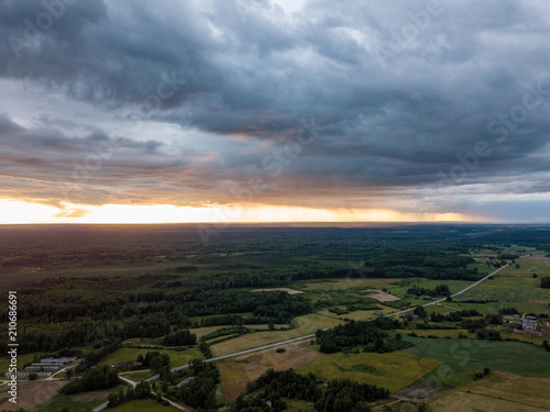 Foto op Plexiglas Chocoladebruin drone image. aerial view of rural area with houses and roads under heavy and dark dramatic rain clouds in summer day. night photo
