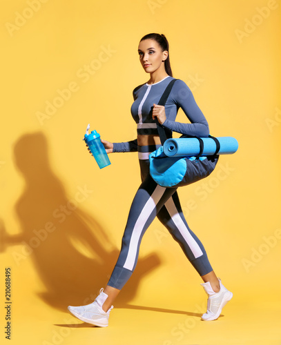 Go to gym! Attractive latin woman in fashionable sportswear on yellow background Wallpaper Mural