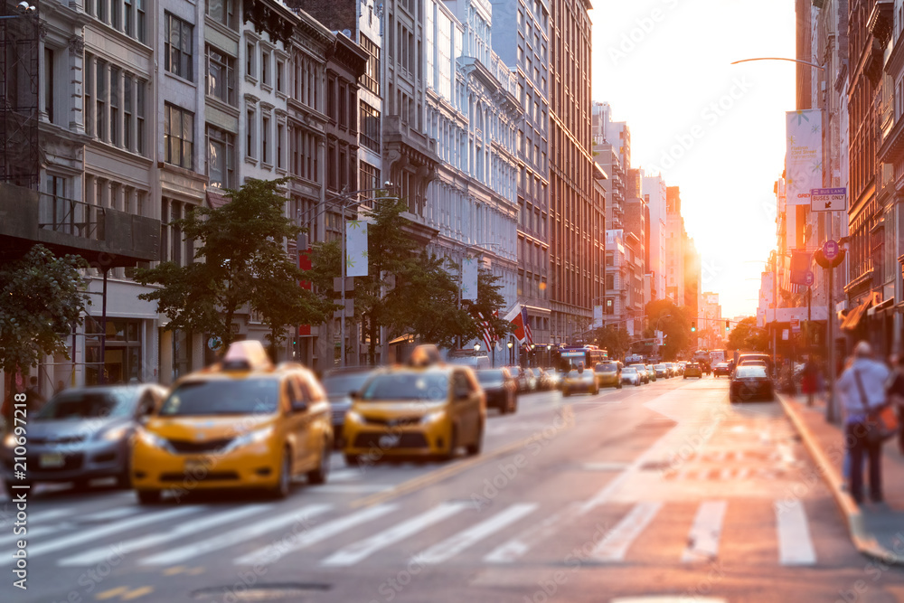 Fototapety, obrazy: Sunlight shines down a busy street in New York City with taxis stopped at the intersection
