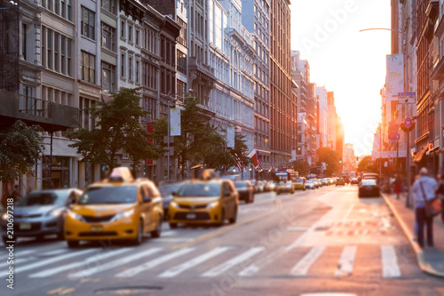 Foto op Canvas New York City Sunlight shines down a busy street in New York City with taxis stopped at the intersection