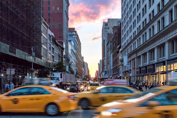 Yellow taxi cabs speeding down Broadway during rush hour in Manhattan, New York City with colorful sunset sky in the background