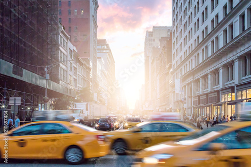 Платно Taxi cabs in motion past crowds of people on Broadway with a colorful sunset in