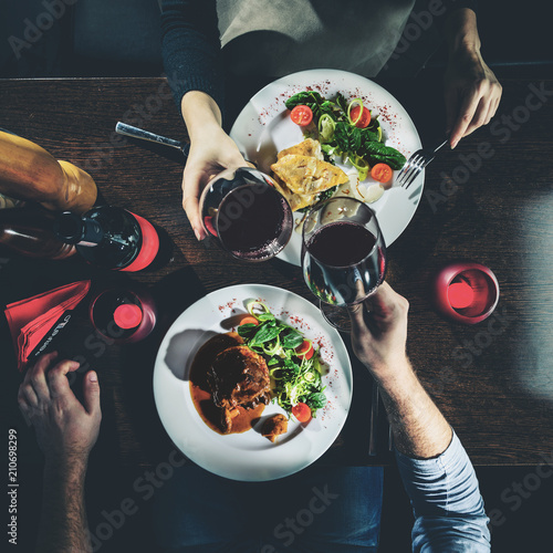 Man and woman having romantic dinner in a restaurant, toned imag
