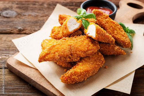 Fototapeta Delicious crispy fried breaded chicken breast strips with ketchup. obraz