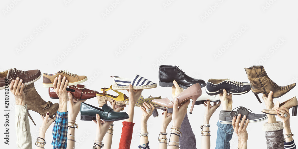 Fototapeta Hands holding different shoes on isolated background