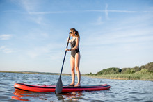 Beautiful Young Woman In Black Swimsuit Paddleboarding On The Lake During The Morning Light