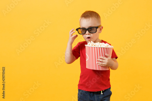 фотография Little cute kid baby boy 3-4 years old in red t-shirt, 3d imax cinema glasses holding bucket for popcorn, eating fast food isolated on yellow background