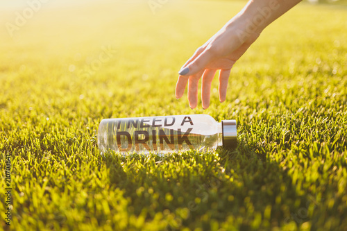 Cuadros en Lienzo Outstretched hand to bottle with fresh clean clear water with text inscription I need drink on green grass on sunshine lawn
