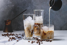 Iced Coffee Cocktail Or Frappe With Ice Cubes And Pouring Cream In Three Different Glasses With Vintage Jezva And Coffee Beans Around On White Marble Table With Grey Concrete Wall At Background.