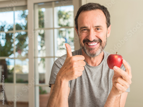 Fotografía Middle age man eating healthy red apple happy with big smile doing ok sign, thum