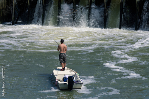Foto op Plexiglas Water Motor sporten A man in a boat fishing near the dam