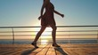 Young woman in retro short dress running on wooden embankment near sea. Girl walking at sunrise or sunset background. Beautiful scene of female legs. Slow motion.