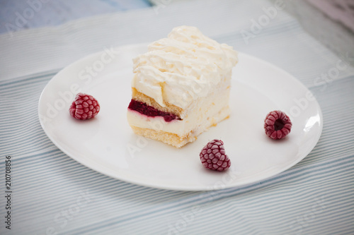 Poster Dessert Dessert of cake and raspberries on a large white plate on a napkin in blue stripes