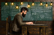 Businessman in suit with laptop at school desk. Bearded man work on laptop in classroom. Man with long beard with notebook on chalkboard. Scientist in glasses on genius face. New technology concept