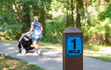 A One Mile Marker Sign Post Beside A Paved Pathway With A Bright Green And Sunny Background With A Mom Walking And Pushing A Stroller.