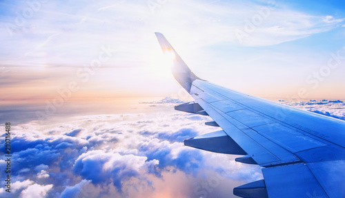 Photo sur Aluminium Avion à Moteur flying and traveling, view from airplane window on the wing on sunset time