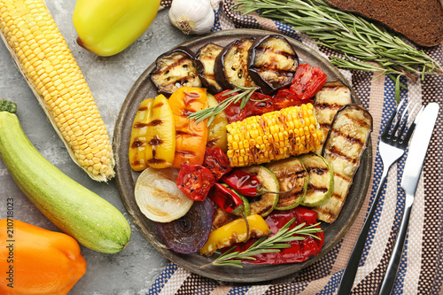 Photo Stands Grill / Barbecue Grilled vegetable on brown cutting board with fork, knife and rosemary