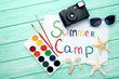 Inscription Summer Camp with retro camera and starfishes on wooden table