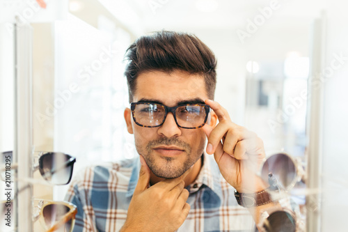 c9cd9b27a5 Handsome young man choosing eyeglasses frame in optical store. - Buy ...