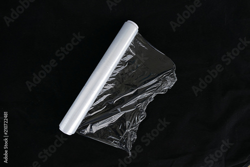 wrapping plastic transparent food film on black background.
