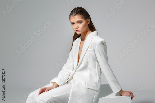 Young and beautiful model on a gray background. High fashion