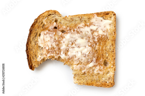 Vászonkép Buttered slice of whole wheat toast isolated on white from above