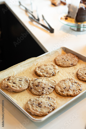 Valokuva  Freshly baked chocolate chip cookies on parchment line baking sheet with space f