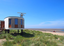 The Old Coastguard Station In Fleetwood With Radar Antennae With Crass Covered Dunes Leading To The Beach On A Summers Day In Bright Sunlight With Blue Sky