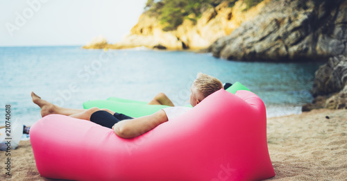 Montage in der Fensternische Rosa hell young hipster relaxing on coastline beach on inflatable lazy air pouffe sofa, person tourist enjoy sunny day on background coast sea waves, seascape perspective vacation, summer seashore