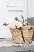 Styled Stock Photo. Feminine Wedding Still Life Composition With Straw French Basket Bag With Pink Peonies Flowers And Eucalyptus Bouquet. Old White Door In The Background. Vertical Composition.