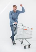 Full Length Portrait Of A Happy Man Running With A Shopping Trolley