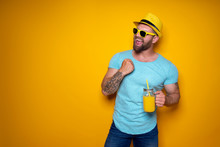 Creative Male In Sunglasses And Summer Clothes In Yellow And Blue Colors Standing Relaxed, Hold Creative Cocktail Bottle With Handle And Straw On Yellow Studio Background
