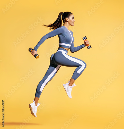 Sporty woman jumping with dumbbells. Photo of active woman in sportswear on yellow background. Dynamic movement. Side view. Sport and healthy lifestyle