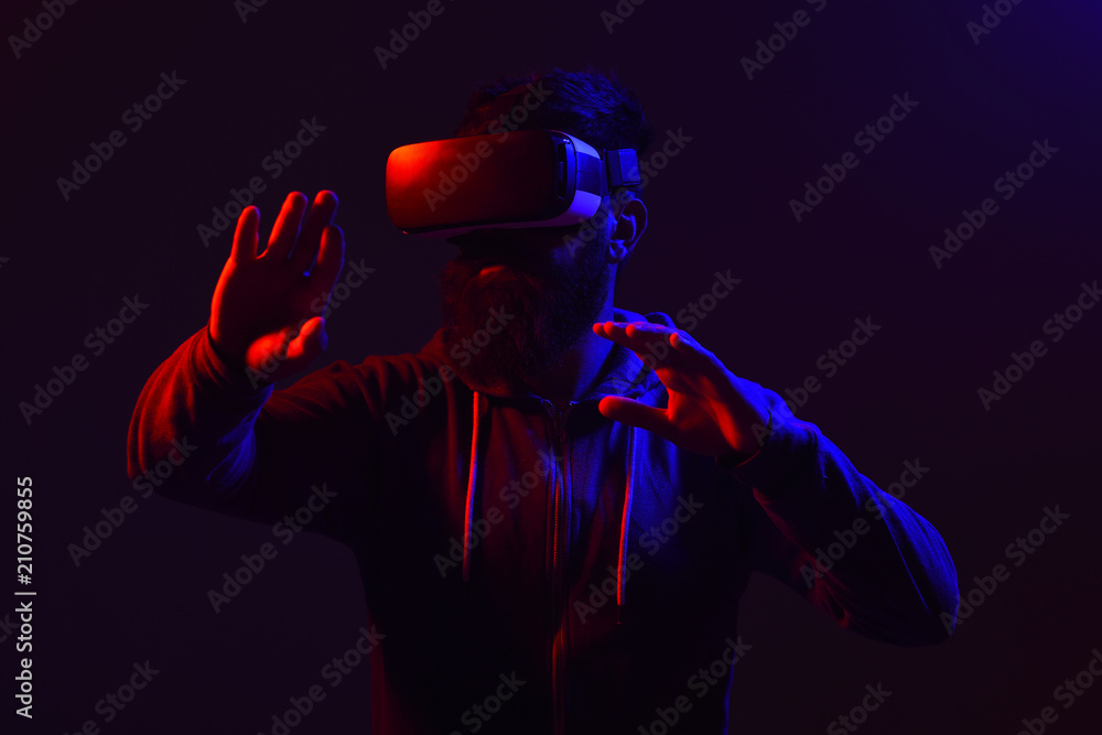 Fototapeta Future technology. Scared man in virtual reality headset. Future. Men using VR headset. Virtual reality glasses. Virtual reality device. Lights. Isolated on black background.
