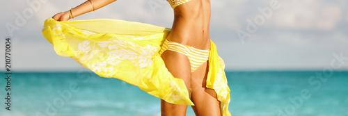 Fotografie, Obraz  Bikini woman with yellow scarf unveiling toned slim thighs and body