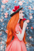 Young Redhead Girl Feels A Bright Sense From The Smell Of Flower In Garden. Very Long Hair. Bright Rose Background. A Beautiful Model With Pale Skin, Red Lips And Rose In Hand. Sense Of Beauty
