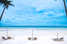 An Empty White Sand Beach With Three Empty Sun Beds And Parasols And An Empty Ocean With Blue Sky