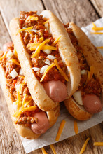 Chili Hot Dogs With Cheese Cheddar, Spicy Ground Beef, Onion And Sauce Close-up. Vertical