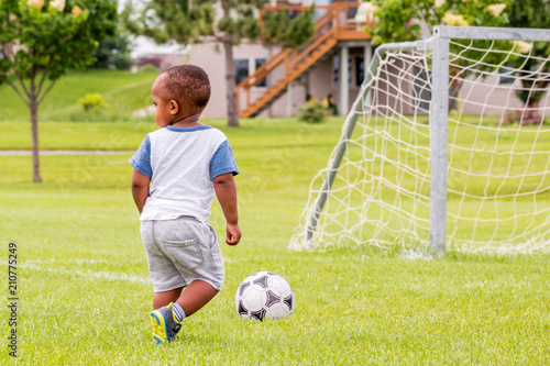 Fotografie, Obraz  A little African toddler is playing soccer at summertime
