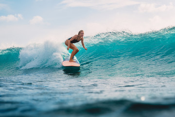 Fototapeta Beautiful surfer girl on surfboard. Woman in ocean during surfing. Surfer and wave