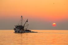 Fishing Boat Sailing Into Sunset On Calm Sea.