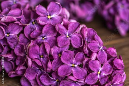 Staande foto Bloemen Lilac flowers macro on the wooden table with the blurred background