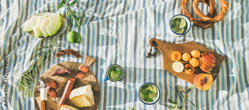 In de dag Picknick Flat-lay of summer picnic set with fruit, cheese, sausage, bagels and lemonade over striped blanket, top view, copy space