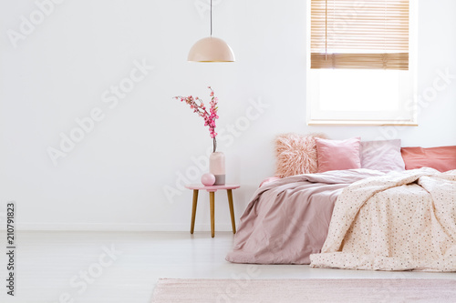 Papiers peints Kiev Lamp above table with flowers in pink pastel bedroom interior with window above bed. Real photo