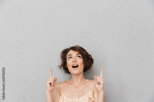 Fotografía  Portrait of a surprised young woman pointing fingers up
