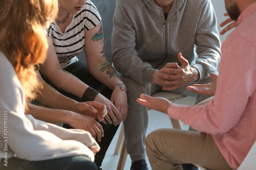 Fototapeta Rebellious youth with tattoos talking about problems during meeting with therapist