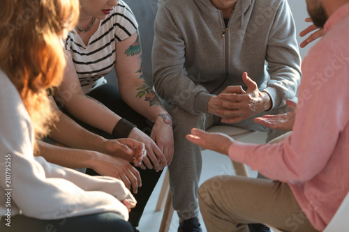 Obraz Rebellious youth with tattoos talking about problems during meeting with therapist - fototapety do salonu